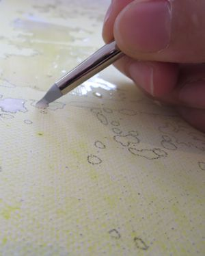 applying masking fluid on canvas with a silicon brush