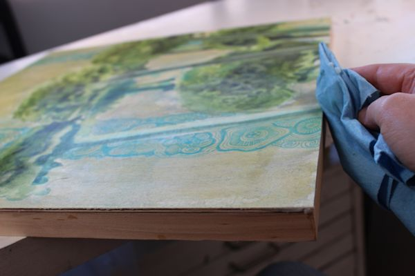 applying dorland's wax medium on the sides of the painting