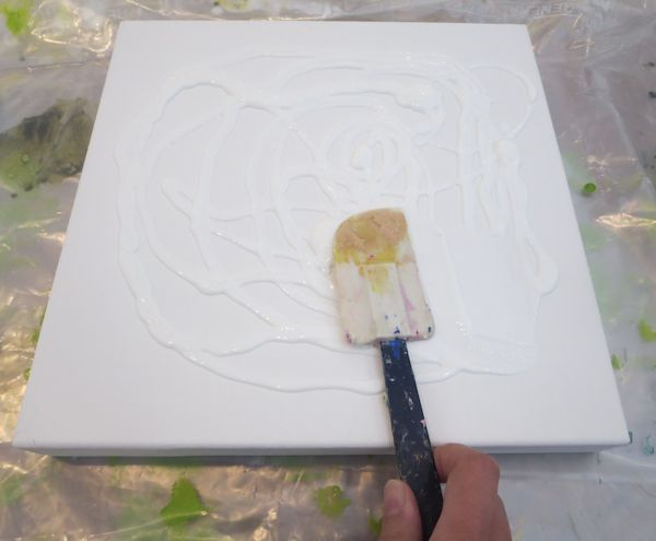 apply gel medium on your canvas with a spatula