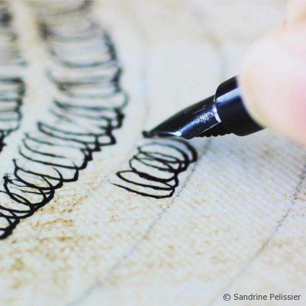 drawing ink loops on canvas with a fountain pen